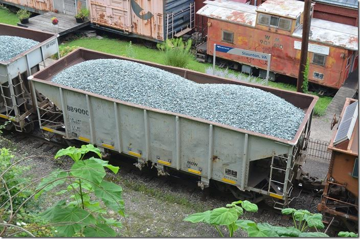 "Buckingham Branch Railroad 9000 hopper is being backed by the Staunton VA station (former C&O) to dump ballast in their shop area at ""C&O Flats."" Some CSX ballast cars were also in the train. 07-30-2015. BB 9000 is shows as ex-BB 1. Definitely unique on BB, but I can't get any prior information on it. BB ballast hopper 9000. Staunton VA."