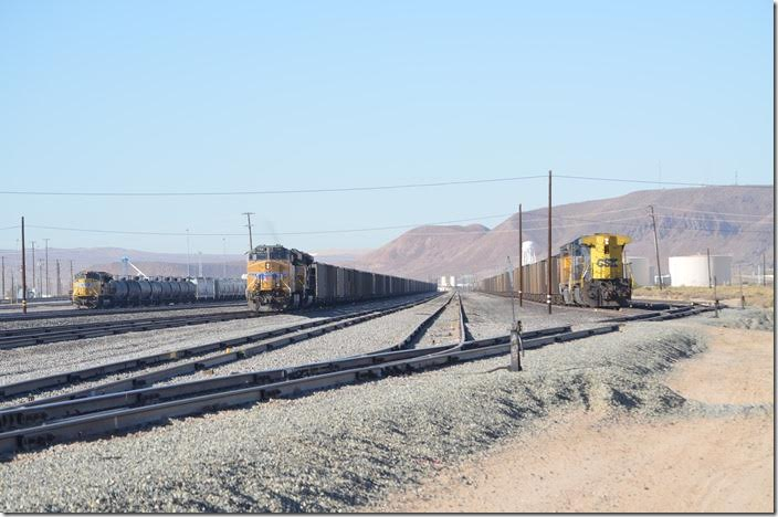 Union Pacific's crew change point is Yermo, a few miles east of Barstow. Yermo isn't much more than a wide spot in the road that the I-15 bypassed. Left to right: UP 8493 on e/b frt, DPU 7768 ready to depart on a w/b coal train, CSX DPU 467 on a w/b coal train. Yes, the score at Yermo is coal trains 2, non-coal 1! Yes, this is environmentally crazy California! Yermo CA.