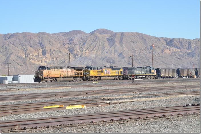 UP 6511-8713-6318 are fueled and pull forward with their coal train. This train is composed of DGHX (Searles Valley Minerals) rapid-discharge hoppers plus a few C&NW fill-ins. This train is likely headed for Mojave and then north on the Lone Pine Br. to Searles. From there it would head over the 30-mile Trona Ry. (owned by Searles Valley Minerals) to the Trona area. Former owner Kerr-McGee Chemical Corp. built the Argus power plant there in 1978. It was the first large industrial power plant in California powered by coal. It serves the company's three area plants. Yermo CA.