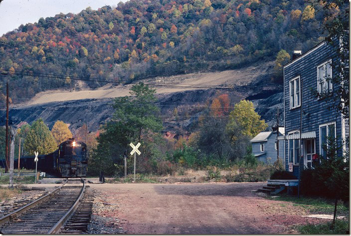 "A westbound mine run comes down the Buffalo SD at Robinette WV, past the post office. C&O 5863-6013 power one of several mine runs that will be needed daily to work all of the mines on Buffalo Creek. Note the ""red dog"" spread out as road material. ""Red dog"" was slate that was the result of spontaneous combustion in coal refuse dumps...like the one in the background being reclaimed. It makes excellent secondary road material. The structure was probably a company store/office at one time. 10-24-1977. C&O Logan, Buffalo, IC SD."