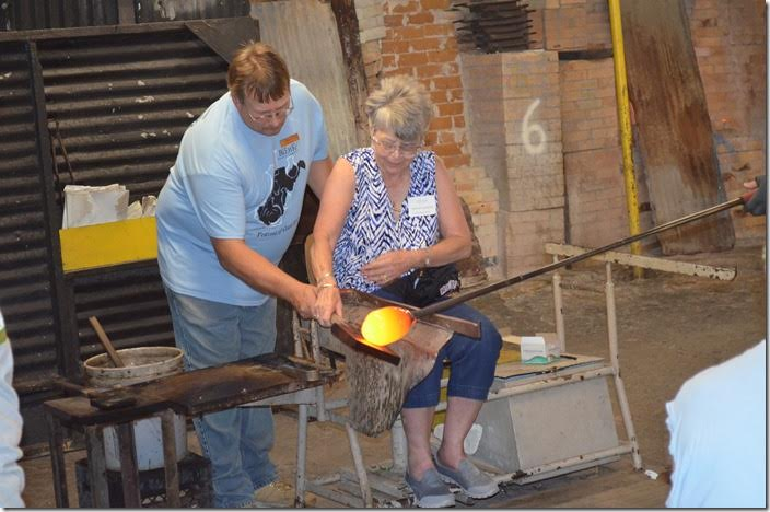The art of glass blowing and shaping was being demonstrated hands-on to a group of visitors. Blenko Glass.