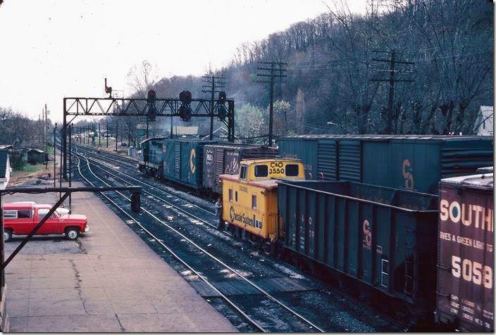 View from RU Cabin as a westbound manifest arrives and 7303 switches the eastbound yard. 11-10-1977. RU Cabin.