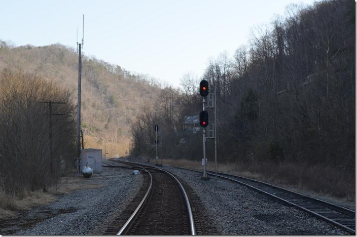 "Approach signal at Levisa Jct. for N760 to stop at Marrowbone siding. Originally the dispatcher had set up a meet at Elkhorn City with a loaded train out of McClure Mine. The 149-car McClure train would not fit in the Elkhorn siding without blocking a crossing. Such a long train would hang out at the south end forcing N760 to stop. The engineer explained that getting started on that 1.5% grade was a ""crap shoot"", and there was a possibility of stalling. The dispatcher admitted that he was not that familiar with the territory but didn't like ""crap shoots"". It was decided to meet at Marrowbone – eight miles north -- instead. This would give the engineer on N760 a chance for a ""run-and-go"" at the steep grade. CSX signal Levisa Jct approach."