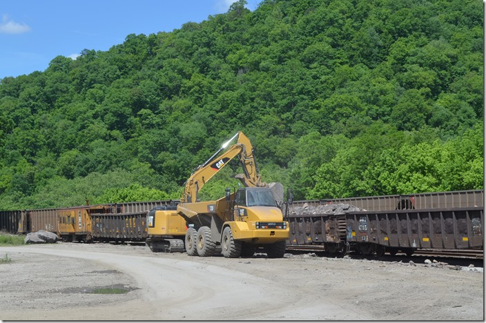 A work train of low side gons is bringing debris from the Robinson Creek Tunnel fire down to Shelby. Here it being unloaded by backhoe and dumped into a vacant lot on CSX property. View 2.