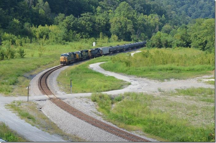 Ethanol train K440 e/b behind 5472-4538-40 have 76 cars on Aug. 27, 2017. This is the site of the Chaparral Coal prep. plant between Pikeville and Fords Branch. The train is approaching the beginning of double track at FO Cabin. A new road and bridge to the industrial site permits this easy shot. With the resumption of Duke Energy coal trains ethanol, grain, etc. trains are rare now. CSX 5472-4538-40. FO Cabin.