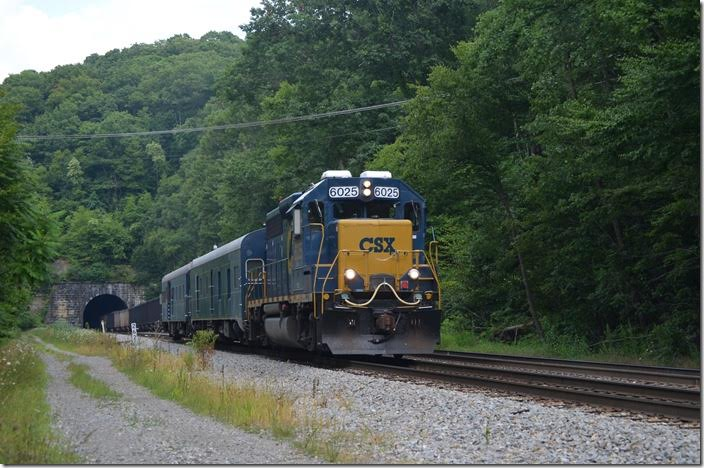 "Track geometry train W001-27 has office car ""Columbus"" and the TGC car. I saw it a couple of weeks later on Big Sandy with the same consist. CSX 6025 is the regular engine. T051 disappears into Kingwood Tunnel and the head end is rolling through Tunnelton. Austen WV."