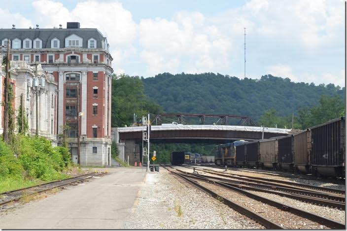 "T051 heads into the yard. On the left is the old B&O station and hotel. The ""beanery"", as I recall was in the ground level of the hotel. I think Bob Jackson's office was also in the old hotel building. A new street bridge is under construction. CSX 719-720. Grafton WV."