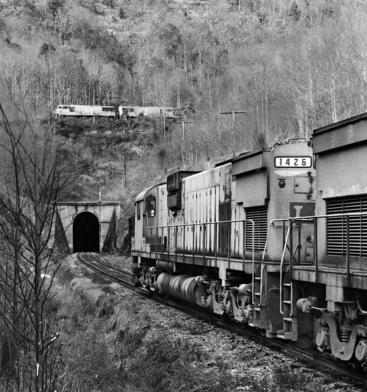 The train on the top was photographed by Everett on November 9, 1975. Train 2nd 864 is dropping downgrade into Hagans, where it will follow the lead into the middle tail track of the switchback. Everett listed the motive power as 1513-1515-1306-1316-1323 (two GE U25Cs and three Alco C420s--although the Alcos are hidden by the trees). The lower shot was taken on December 28, 1975--a few weeks after the first. L&N 1st 864 was led by 1426-1412-1513 (an Alco C630, C628, and a U25C--in the fact the same unit pictured on the upper train from the previous month). Everett noted the lower train had 75 cars.