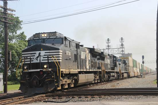 NS 9763, 8434, and 7570 crossing the diamond with a stack train.
