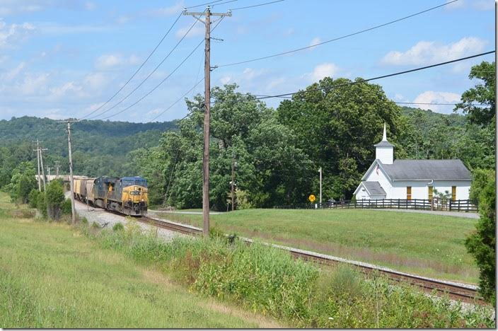 CSX e/b grain train behind 128-987 rolls by the picturesque Methodist church at Kavanaugh KY, on the Big Sandy SD. 06-21-2015. CSX 128-987 Kavanaugh KY. View 2.