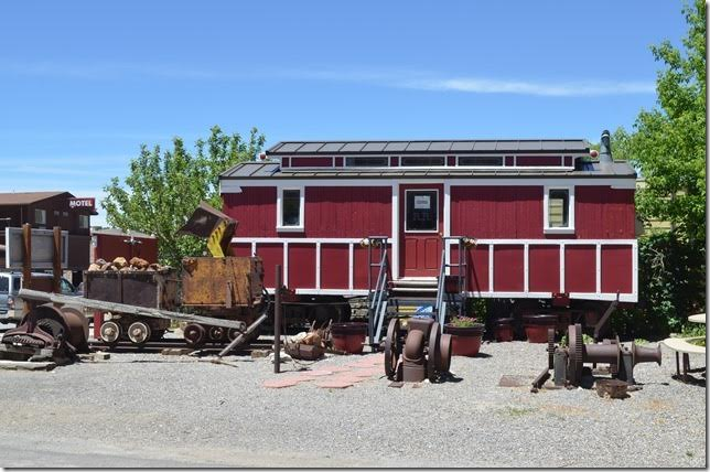 "Surrounded by various mining implements, this ""crew car"" is the only item of the abandoned Eureka & Palisade Railroad that survives. It is now an economic development office. The E&P was abandoned in the mid-1930s."