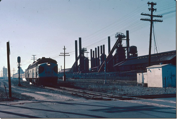 Heading north to Atlanta and eventually Washington, No. 2 passes the closed U. S. Pipe & Foundry blast furnaces at 32nd St. The former Sloss-Sheffield Steel & Iron landscape is now a city park and can be toured. By the way Sloss never took the process far enough to to produce steel – SSS&I and USP&F only produced iron for pipe, etc. Birmingham's skyline is in the background. US 11 and L&N is on the other side of the mill. 01-29-1979.